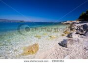 stock-photo-a-beautiful-white-stone-beach-with-clear-blue-water-off-the-coast-of-korcula-49300354