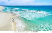 stock-photo-surfer-on-pretty-beach-and-ocean-with-sailboat-and-clouds-in-distance-14292274