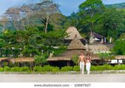 stock-photo-a-young-couple-walking-on-beach-with-resort-behind-them-10687927