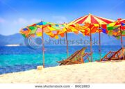 stock-photo-deck-chairs-and-umbrellas-overlooking-thai-beach-8601883